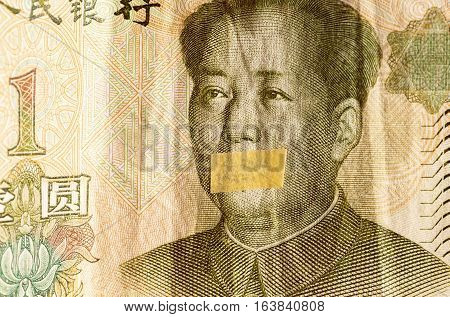 Portrait of the communist revolutionary Mao Zedong with mouth closed on the banknote of Chinese Yuan, as a symbol of the instability of the modern economy