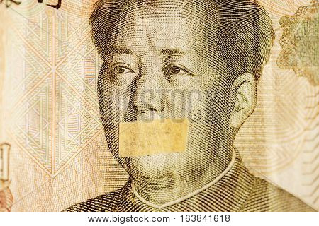 Mao portrait leader of China with closed mouth on a banknote of Chinese Yuan, as a symbol of the instability of the modern economy