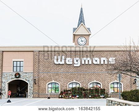 Fairfax, USA - November 30 2016: Wegmans grocery store facade and sign with people and Christmas wreath decorations