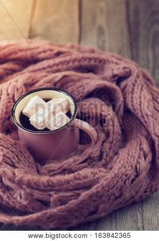 pink mug with a hot drink and marshmallow wrapped in a pink scarf