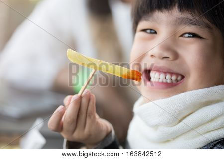 Beautiful laughing little girl sitting at table and eating French fries