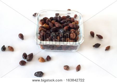 Top view of dried rose hips berries in square transparent bowl and scattered berries on white background