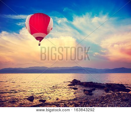 Hot Red Air Balloon Flying over Sea at Sunset. Blue Sky Background with Beautiful Clouds. Pebble Beach and Evening Seascape. Coastline and Mountains on the Horizon. Toned and Filtered Photo.