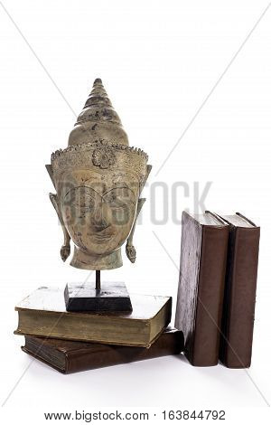 Buddhist wisdom. Ethics religious and spiritual education symbolized by a statue of the Buddha with old leather bound books.