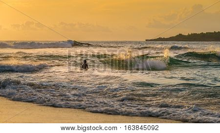 Local Kids surf on Waves in Sunset light, Beautiful Crystal Bay, Nusa Penida, Bali