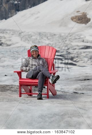 Woman Sits in Red Chair on Athabasca Glacier on a sunny summer day