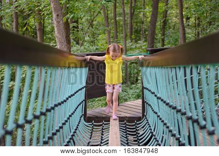 girl climbing on rope ladder at the park