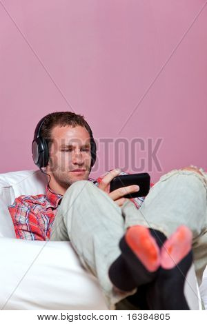 A man sat in an armchair wearing headphones listening to music on his mp3 player.