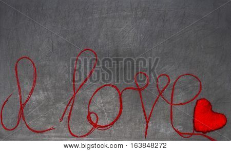 I love you. the inscription is made of red thread on a black chalkboard