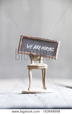 phrase we are hiring and golden chair on a gray background