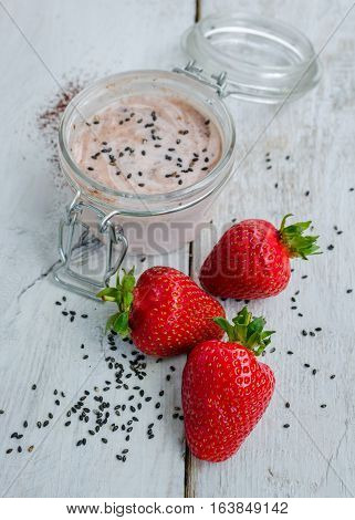 Homemade yogurt in a jar with strawberry seeds and cacao. Dessert with strawberries on a white wooden background. Fresh strawberry with yogurt. Selective focus. Shallow depth of field. Vertical.