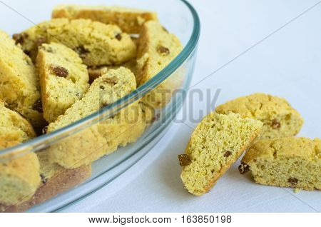 Homemade raisins cookies on white background with place for text. Glass dish with freshly baked raisin cookie. Healthy breakfast. Tasty cookies for an afternoon snack. Selective Focus. Copy space.