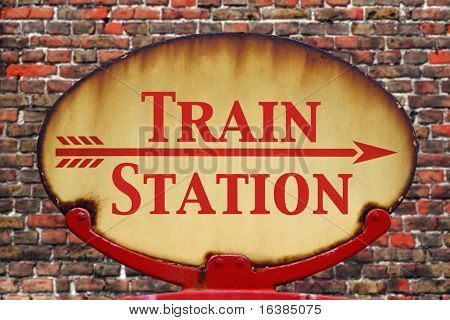 A rusty old retro arrow sign with the text Train station