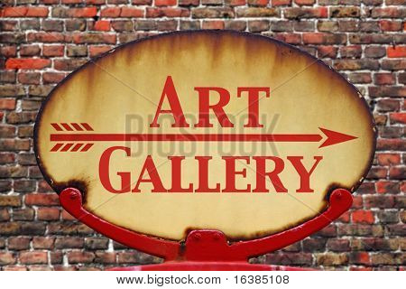 A rusty old retro arrow sign with the text Art gallery