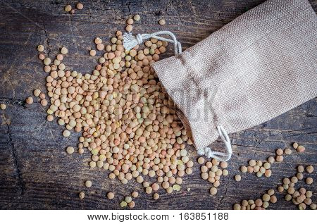 Brown dried lentils in a burlap bag on wooden board background. Dry Organic Brown Lentils. Healthy vegetarian food concept. Top view.