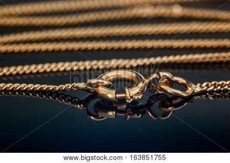 Gold necklace chain clasp or closure closed on reflecting glass table