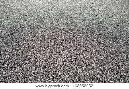 Asphalt black surface with gravel closeup as background