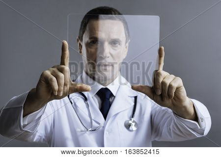 Discover it. Handsome concentrated delighted doctor posing with medical glass and looking at it attentively while standing on a grey background.