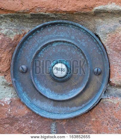 a rusty door bell with the writing press