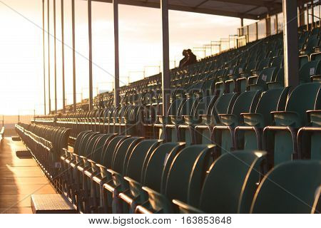 Symmetrical regular pattern grandstand seating arrangement at sunset