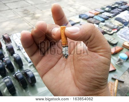 close up fag end in hand on day