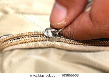 close up hand pulling a zip bag