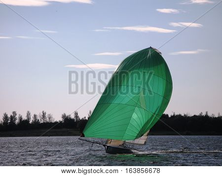 Dinghy sailboat sailing on a lake under a blue sky