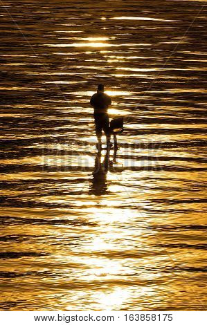 Fisherman fishing from a platform at sunrise. Lake is golden in color. Pyramid Lake NV