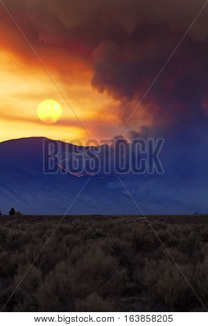 Wildfire Burning In The Nevada Desert At Sunset With Smoke, Fire And Sun.