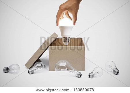 Hand of a businessman holding a turned on LED light bulb coming out from a brown paper box surrounded by old incandescent light bulbs / Business with new idea and innovation concept