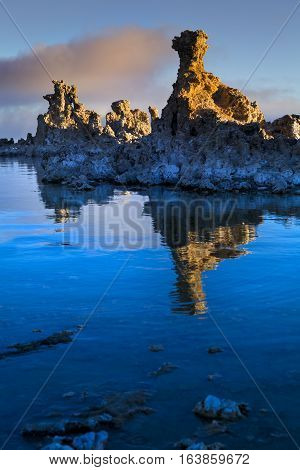 Tufa formation at Mono Lake California. Rock is reflected in water in the foreground.