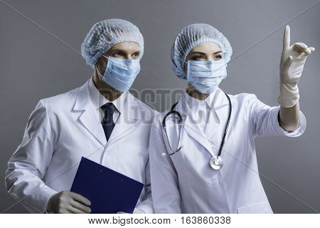Important profession. Concentrated handsome man and beautiful woman wearing face masks and surgical caps and working as doctors while posing on a grey background.