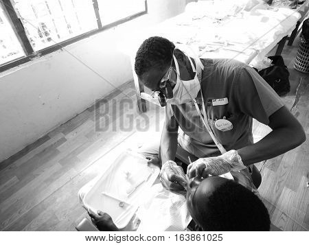 GHANA, WEST AFRICA - OCT 30, 2015: Dentist preform teeth cleaning on little girl during missions trip in accra