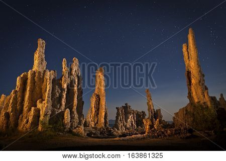 Tufa formation at Mono Lake at night with stars in the sky. Shallow depth of field with focus on lit prominent rock formations