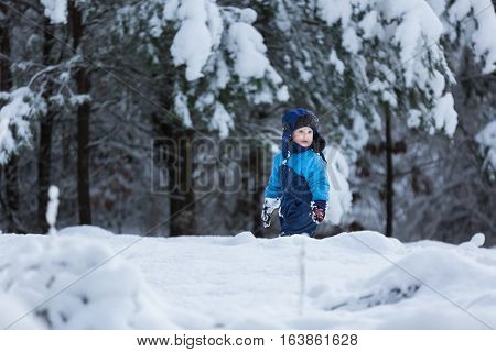 Boy playing in big snow in winter. Happy caucasian child playing in snow.