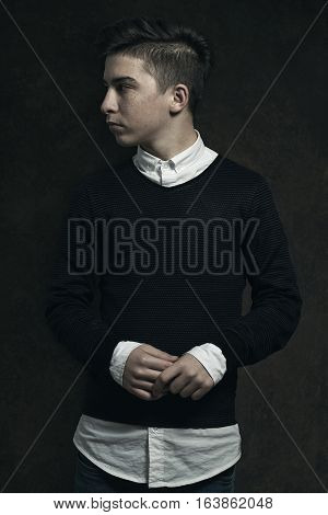 fashioned boy looking sideways in front of grunge background