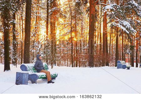 Scenic winter landscape - snow-covered trees in a city Park during sunset. On the bench sits a young frozen man in a hooded jacket with his hands in pockets.