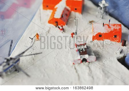 scenes from the life of the helicopter brought the repairmen on the Russian polar station. The orange houses on the background of white snow in miniature