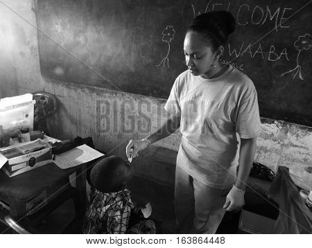 GHANA, WEST AFRICA - OCT 28, 2015: Female nurse checks temperature of boy during missions trip in accra
