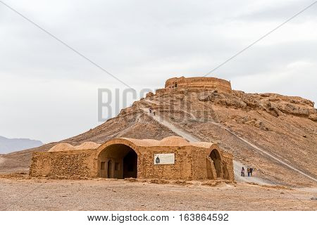 YAZD, IRAN - MAY 4, 2015: Disused building at the foot of the hill and the tourists sightseeing the Tower of Silence.