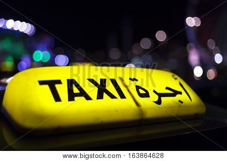 Illuminated yellow taxi sign in the city of Abu Dhabi United Arab Emirates
