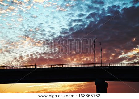 sunset over the bridge the bridge in the sun beautiful yellow-orange clouds over the bridge blue-orange sky over the road man walking on the bridge