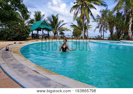 Lady happy pretty relax with swimsuit on pool in Chumphon province Thailand.