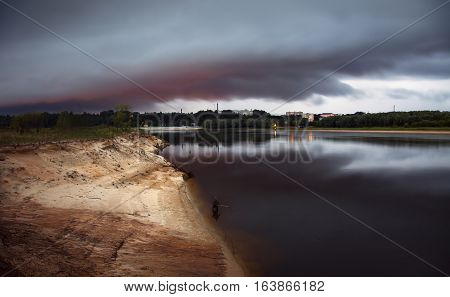 large rainy cloud over the river dusk over the city a fisherman in the water fishing evening city