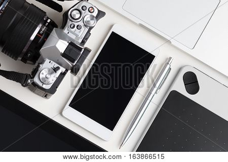 Top view of designer blogger or photographer working table. Graphic tablet tablet pc laptop smartphone and photo camera laying on white table.