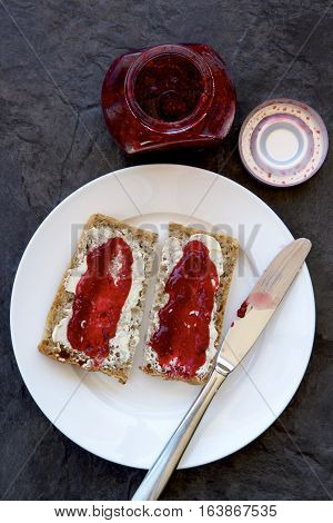 Strawberry jam spread on spelt bread on a plate with a knife.