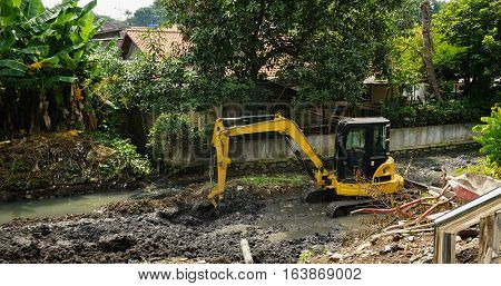 An excavator scrapping mud from river photo taken in Semarang Indonesia java