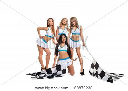 Sexy beautiful bronezed girls dressed in formula one race style and high heel platform shoes posing cheerfully and flirty with two black and white flags in studio.