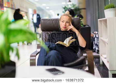 Thougtful woman sitting by wooden table and reading book in public library.