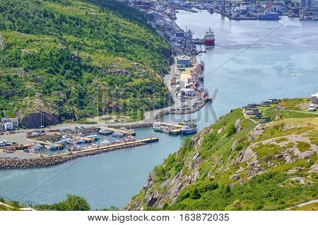 Commerce, trade, ships of all kinds lined up along St John's Harbour in Newfoundland Canada.  Boats slowly move about amongst those docked in harbour.